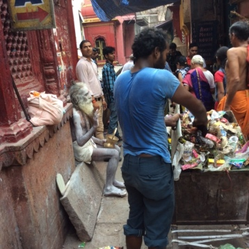 Sadu on street corner by temple